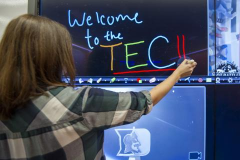 Woman writing Welcome to TEC on a blackboard