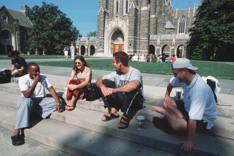 Duke students sit on steps in front of Duke Chapel