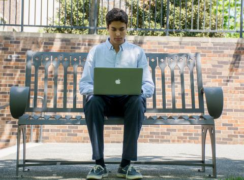 Student sitting at bench outside working on laptop