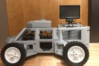 Gray 3d printed vehicle with screen monitor mounted on top,.