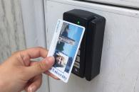 Person tapping a DukeCard to an exterior door reader.
