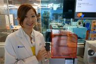 Dr. Alice Wang holds a 3D printed heart in front of a speclialized 3D printer