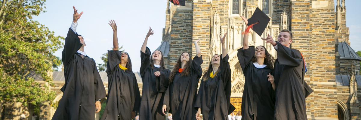 Duke grads throw up their caps in front of the chapel